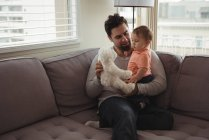 Father and baby playing with teddy bear on sofa in living room at home — Stock Photo