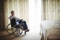 Homme âgé assis en fauteuil roulant dans la chambre à coucher à la maison — Photo de stock
