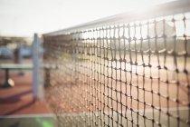 Крупный план сетки на теннисном корте при солнечном свете — стоковое фото