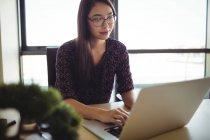 Молодая предпринимательница, работающая над ноутбуком в офисе — стоковое фото