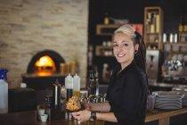 Portrait de serveuse tenant un plateau de muffins au comptoir du café — Photo de stock