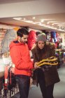 Casal selecionando sapatos de neve juntos em uma loja — Fotografia de Stock