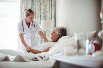 Женщина-врач взаимодействует со старшим пациентом дома — стоковое фото