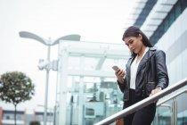 Mulher usando telefone celular fora do escritório — Fotografia de Stock