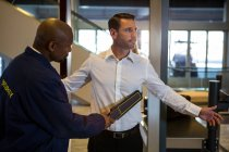Security guard frisking a passenger at airport terminal — Stock Photo