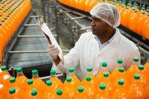Высокоугловой вид мужчины, читающего буфер обмена во время проверки бутылок на соковом заводе — стоковое фото