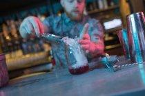 Barman mettant glace dans le récipient pendant la préparation de cocktails au bar — Photo de stock