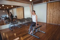 Trainer helping woman while practicing pilates in fitness studio — Stock Photo