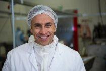Retrato de açougueiro sorridente na fábrica de carne — Fotografia de Stock