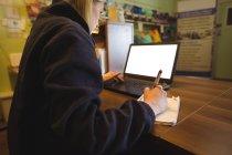 Жінка, використовуючи ноутбук і писати блокнот в офісі — стокове фото