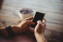 Femme utilisant un téléphone portable dans le café — Photo de stock