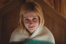 Retrato de mujer hermosa envuelta en manta de lana en el dormitorio en casa - foto de stock