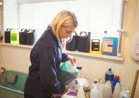 Femme versant shampooing pour chien dans une bouteille au centre de soins pour chiens — Photo de stock
