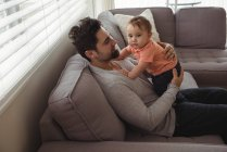 Father playing with his baby on sofa in living room at home — Stock Photo
