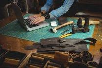 Meados de seção de artesão usando laptop na oficina — Fotografia de Stock