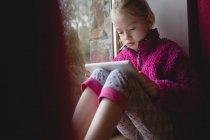 Ragazza seduta sul davanzale della finestra e utilizzando tablet digitale a casa — Foto stock