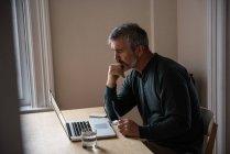 Uomo seduto con computer portatile in soggiorno a casa — Foto stock