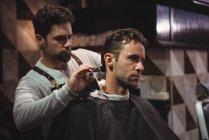Мужчина стрижется парикмахером с ножницами в парикмахерской — стоковое фото