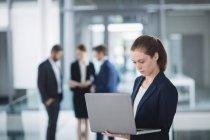 Empresaria de pie en la oficina y el uso de ordenador portátil - foto de stock