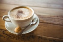 Close-up of coffee cup with saucer and spoon on table in cafe — Stock Photo