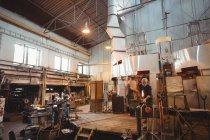 Equipe do ventilador de vidro que dá forma a um vidro no blowpipe na fábrica de sopro de vidro — Fotografia de Stock