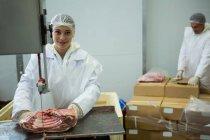 Portrait de boucher femelle coupant la viande avec la machine de découpe de viande — Photo de stock