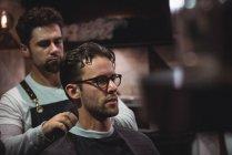 Barbeiro colocando capa sobre cliente na barbearia — Fotografia de Stock