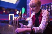 Женщина-бармен с помощью мобильного телефона у стойки в баре — стоковое фото
