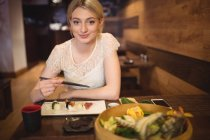 Portrait de femme souriante mangeant des sushis au restaurant — Photo de stock