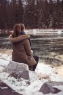 Rear view of woman sitting on river bank in winter — Stock Photo