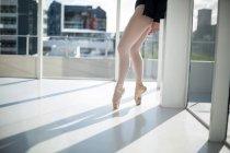 Sección baja de bailarina practicando danza de ballet en el estudio - foto de stock