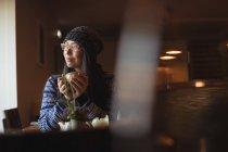 Задумчивая женщина пьет кофе в кафе — стоковое фото