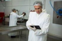 Technicien utilisant tablette numérique à l'usine de viande — Photo de stock