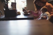 Mid adult woman with baby daughter using mobile phone in cafe — Stock Photo
