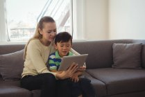 Mother and son using digital tablet in living room at home — Stock Photo