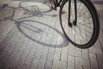 Vélo penché par balustrade de promenade à la lumière du soleil — Photo de stock