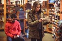 Жінка вибір взуття в магазині під час людина за допомогою мобільного телефону — стокове фото
