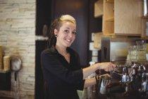 Retrato de garçonete usando a máquina de café no café — Fotografia de Stock