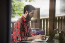 Man using laptop with wine glass on table in bar — Stock Photo