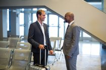 Деловые люди, взаимодействующие друг с другом в зале ожидания аэропорта — стоковое фото