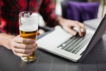 Mid section of man using laptop with glass of beer on table in bar — Stock Photo