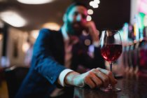 Homme d'affaires tenant un verre de vin dans un bar — Photo de stock