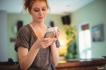 Mulher bonita usando celular enquanto tomando café na cozinha em casa — Fotografia de Stock