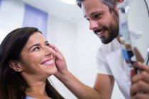 Врач проверяет кожу пациента после косметического лечения в клинике — стоковое фото