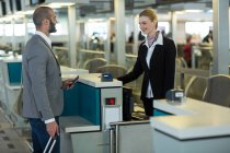 Smiling commuter interacting with attendant at check-in counter in airport terminal — Stock Photo