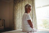Femme âgée réfléchie assise sur un lit dans la chambre à coucher à la maison — Photo de stock