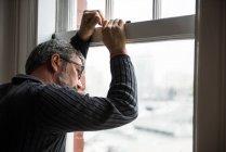 Uomo premuroso che guarda attraverso la finestra a casa — Foto stock