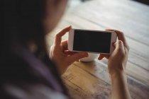 Mujer usando el teléfono móvil en la cafetería - foto de stock