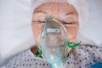 Gros plan d'un patient âgé portant un masque à oxygène couché sur un lit d'hôpital — Photo de stock