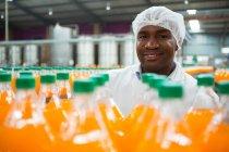 Портрет счастливого мужчины, стоящего у бутылок с апельсиновым соком на заводе — стоковое фото